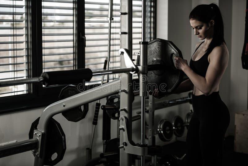 Mujer que añade el peso en una barra como ella entrenamiento en gimnasio de la aptitud imágenes de archivo libres de regalías