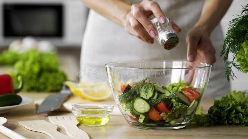 Mujer que añade la sal en el bol de vidrio vegetal de la ensalada, atención sanitaria, el salar excesivo imagen de archivo