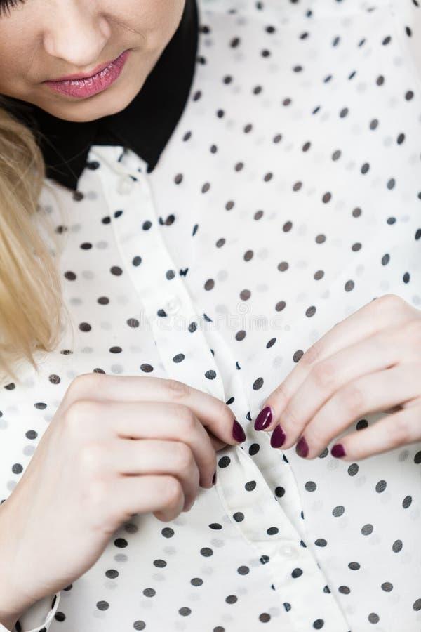 Mujer que abotona los botones en su camisa punteada imagenes de archivo