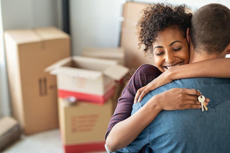 Mujer que abraza al hombre y que lleva a cabo las teclas HOME imagen de archivo libre de regalías