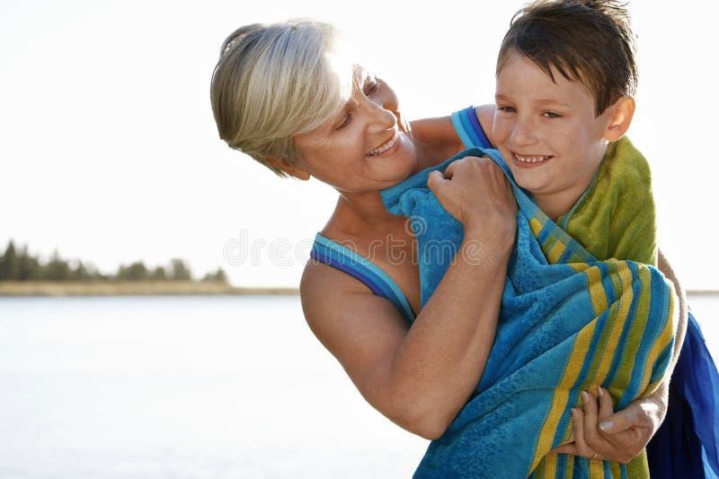 Mujer que abraza al nieto envuelto en toalla imagenes de archivo