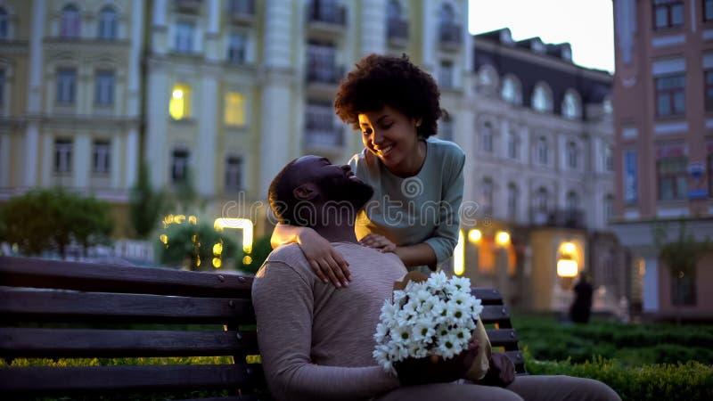 Mujer que abraza al novio, mirando con el amor, sosteniendo las flores, fecha romántica imagenes de archivo