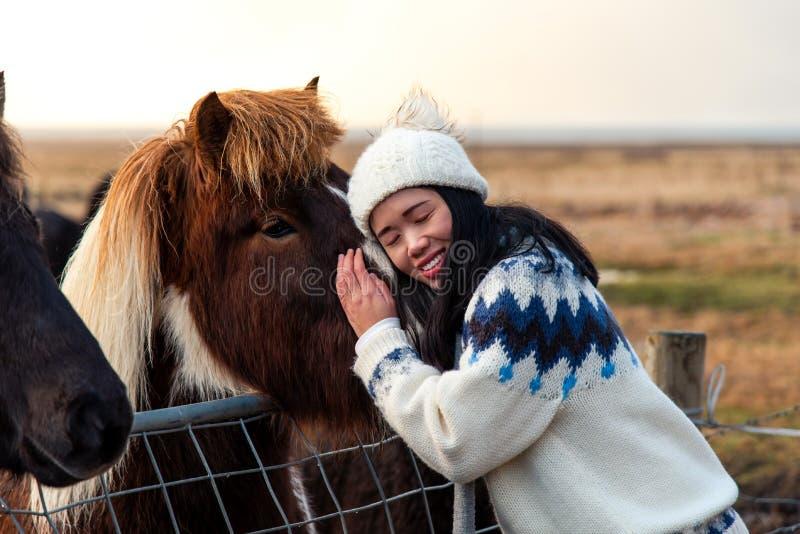 Mujer que abraza con el caballo islandés en el viaje por carretera de Islandia foto de archivo