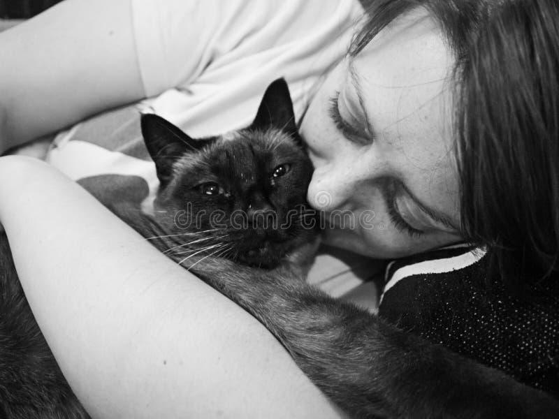 Mujer que abraza el gato fotografía de archivo