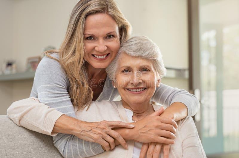 Mujer que abraza a la madre con amor foto de archivo