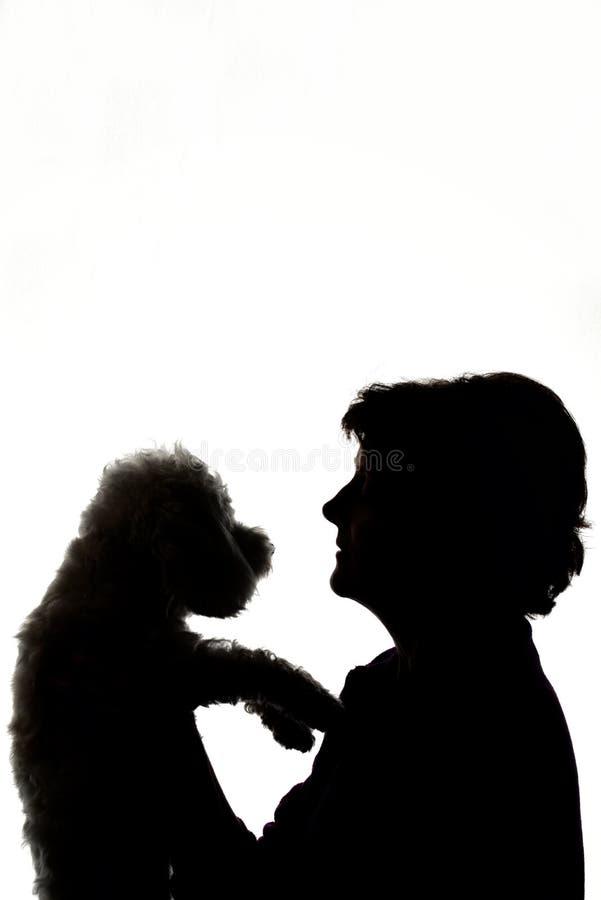 Mujer que abraza la silueta del perro imágenes de archivo libres de regalías