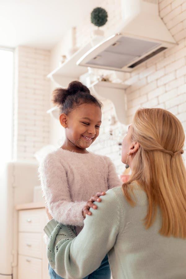 Mujer que abraza su situación del niño en acogida en la cocina imagenes de archivo