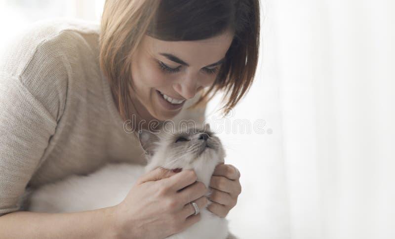 Mujer que abraza y que acaricia su gato fotografía de archivo