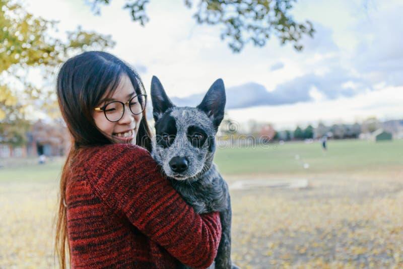 Mujer que abraza y que mira blando su perrito del australiano del animal doméstico fotografía de archivo
