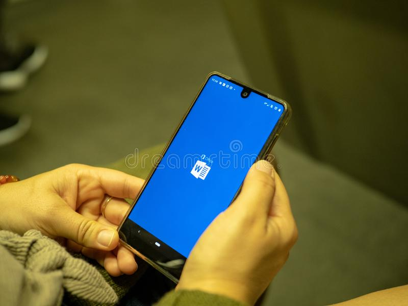 Mujer que abre el app de la palabra de Microsoft Office 365 con el logotipo en la pantalla de Android mientras que conmuta en el  fotografía de archivo libre de regalías