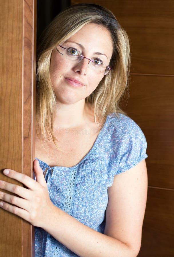 Mujer que abre la puerta de su casa fotografía de archivo libre de regalías