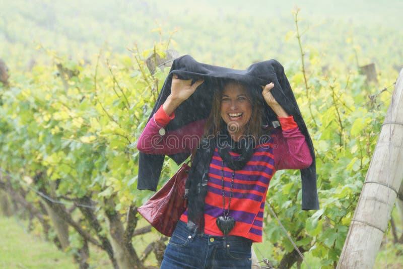 Mujer que abriga de la lluvia en viñedo fotos de archivo
