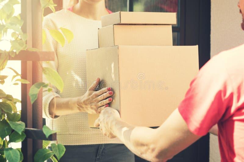 Mujer que acepta un servicio a domicilio de cajas del repartidor fotos de archivo libres de regalías