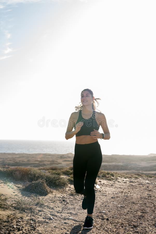 Mujer que activa que corre en el desierto imagenes de archivo
