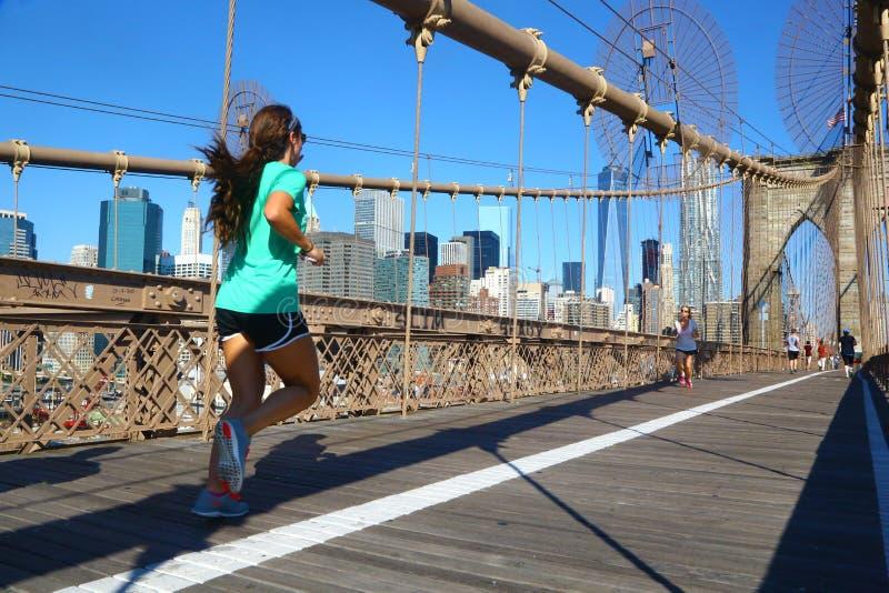Mujer que activa en el puente de Brooklyn, Nueva York foto de archivo