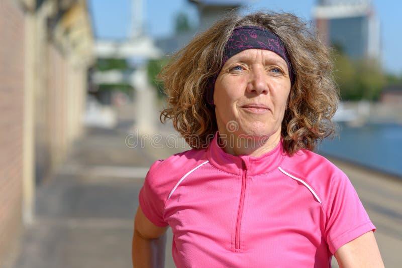 Mujer que activa junto a un canal o a un r?o urbano imagenes de archivo
