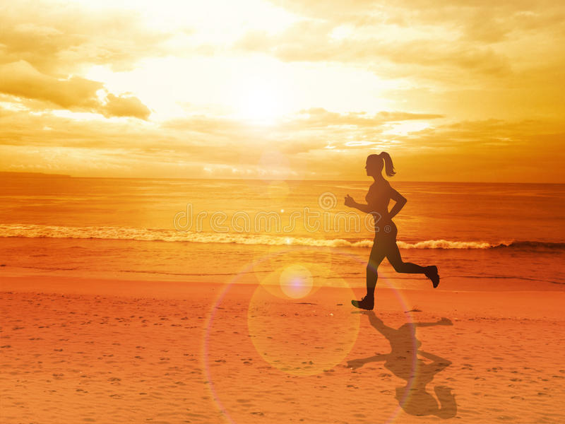 Mujer que activa solamente en la puesta del sol hermosa en la playa imagenes de archivo
