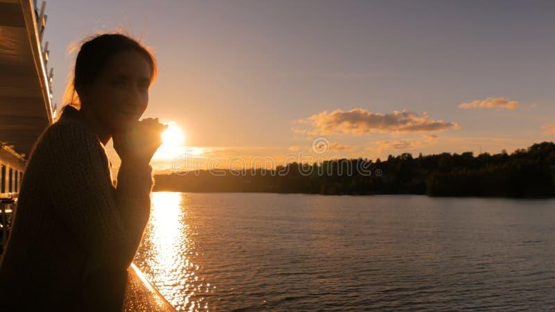 Mujer que admira puesta del sol de la cubierta del barco de cruceros imagenes de archivo
