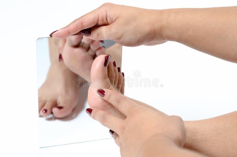 Mujer que admira sus pies en un espejo foto de archivo libre de regalías