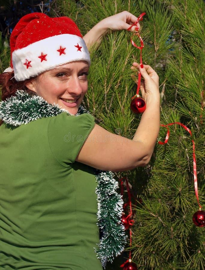 Mujer que adorna el árbol de navidad foto de archivo libre de regalías