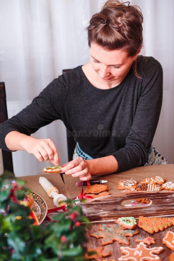 Mujer que adorna el pan de jengibre de la Navidad con helar fotografía de archivo