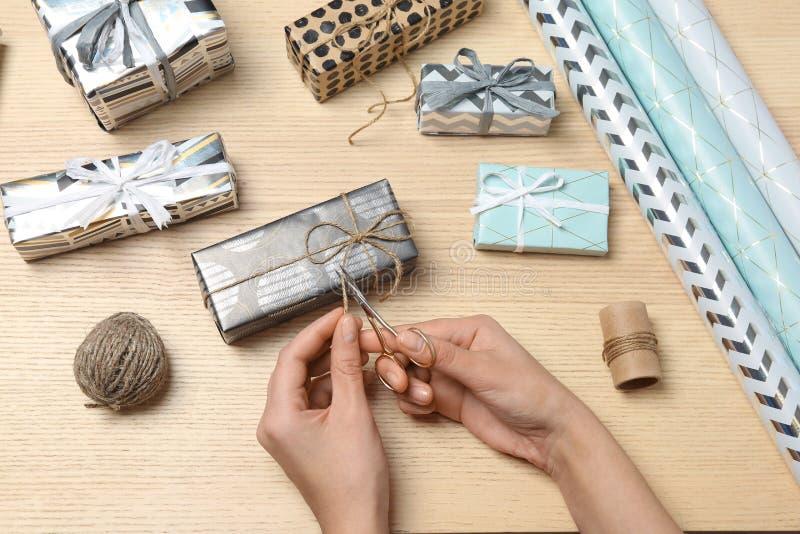 Mujer que adorna la caja de regalo en fondo de madera imágenes de archivo libres de regalías