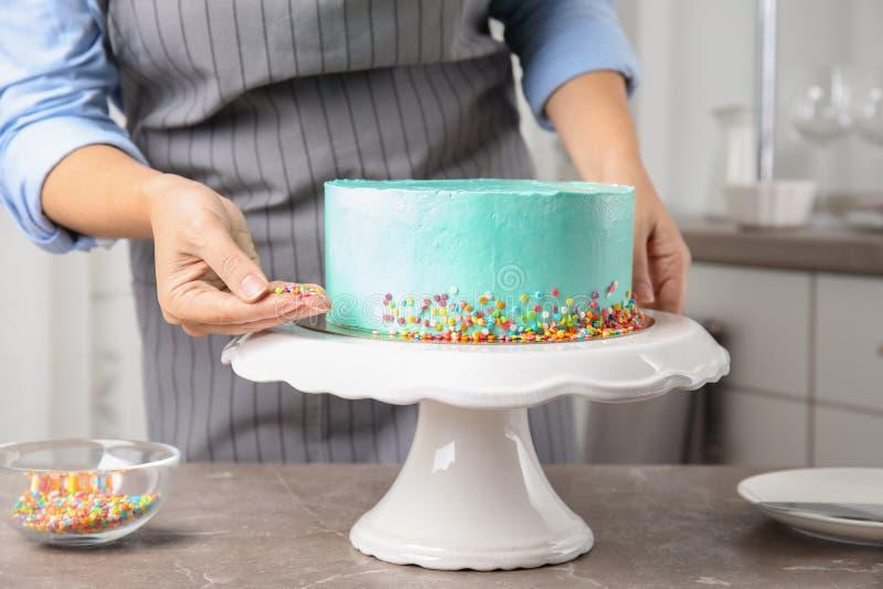 Mujer que adorna la torta de cumpleaños deliciosa fresca en cocina foto de archivo