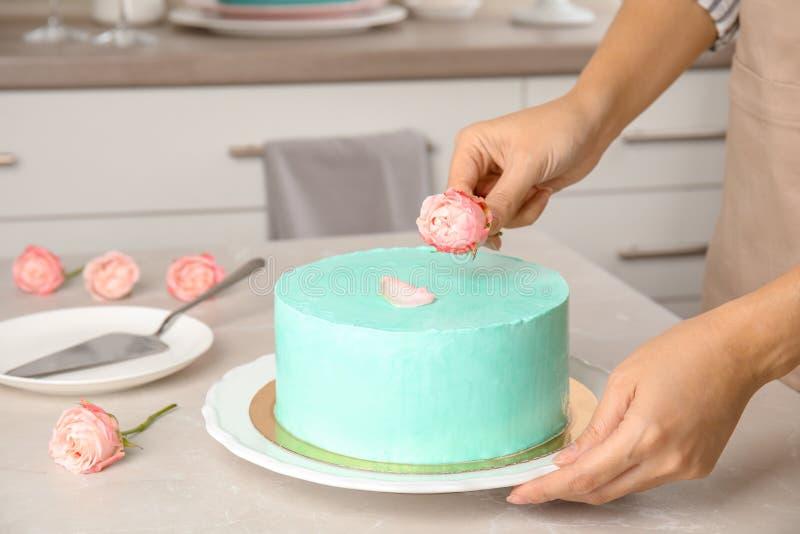 Mujer que adorna la torta de cumpleaños deliciosa fresca en cocina foto de archivo libre de regalías