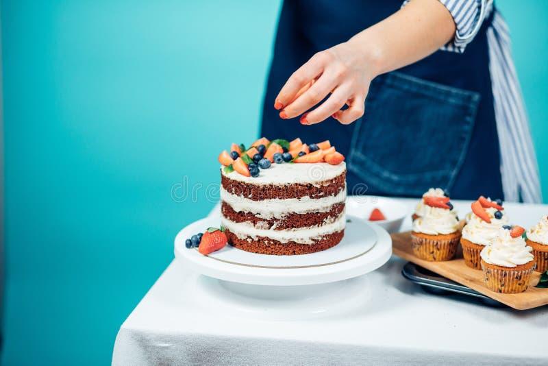 Mujer que adorna la torta deliciosa imagenes de archivo