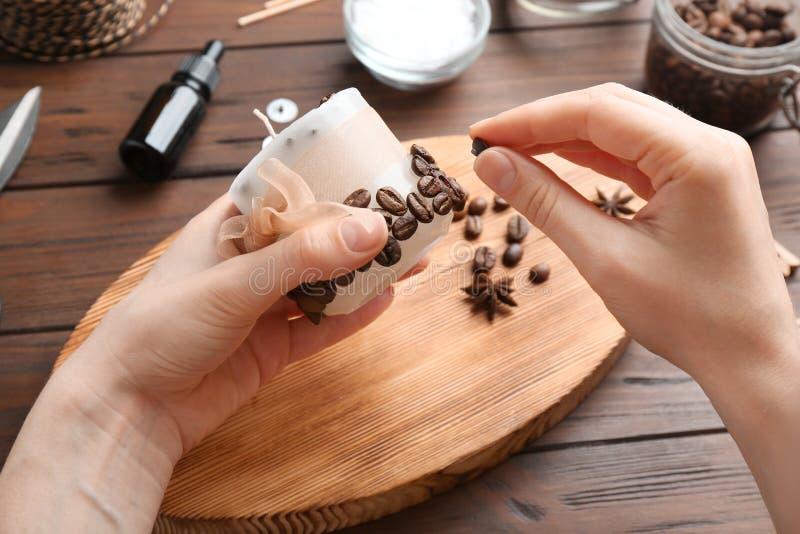 Mujer que adorna la vela hecha a mano con los granos de café imagen de archivo