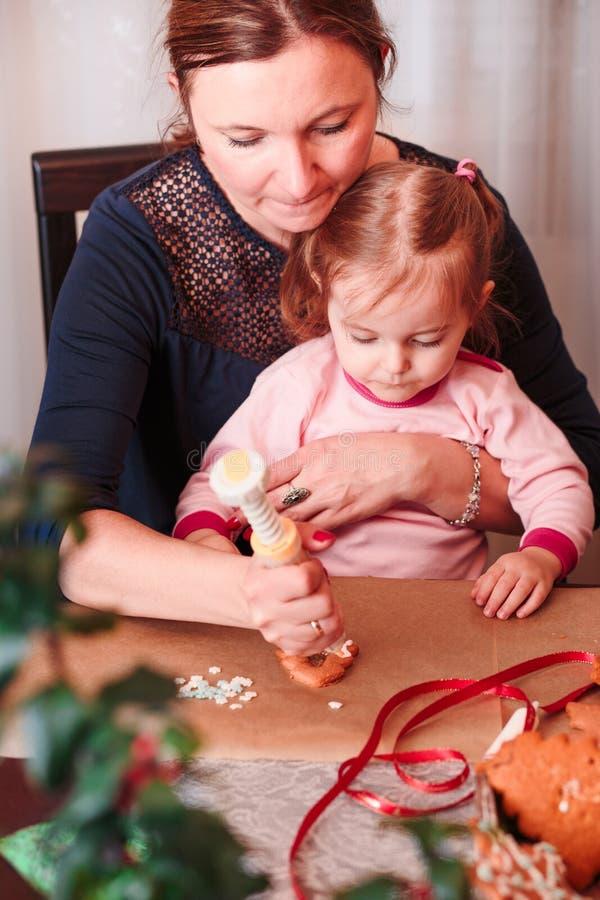 Mujer que adorna las galletas cocidas del pan de jengibre de la Navidad con frosti imagenes de archivo