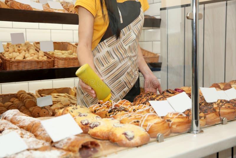Mujer que adorna los pasteles en tienda de la panadería imágenes de archivo libres de regalías