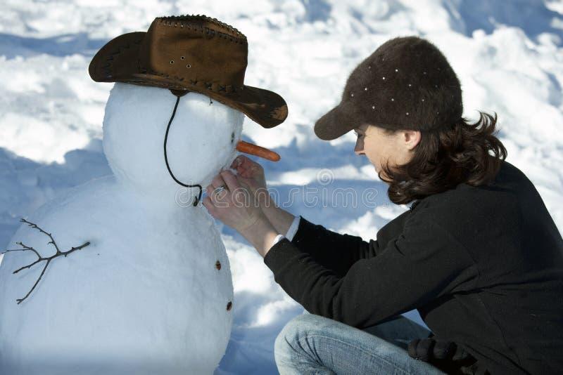 Mujer que adorna un muñeco de nieve imagen de archivo