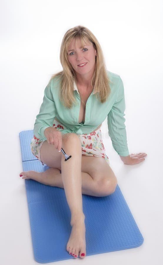 Mujer que afeita las piernas foto de archivo libre de regalías