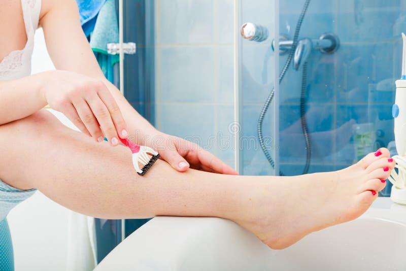 Mujer que afeita las piernas con la maquinilla de afeitar en cuarto de baño imagenes de archivo