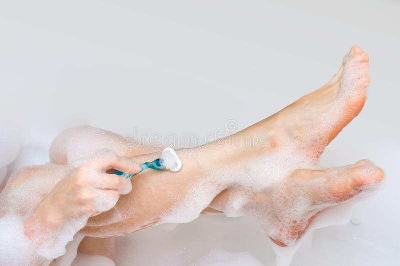 Mujer que afeita las piernas con la maquinilla de afeitar en cuarto de baño foto de archivo libre de regalías