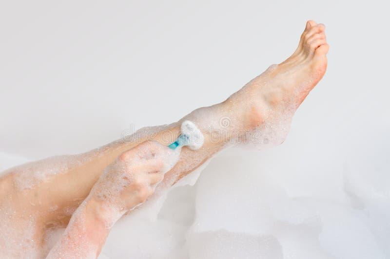 Mujer que afeita las piernas con la maquinilla de afeitar en cuarto de baño imagen de archivo libre de regalías