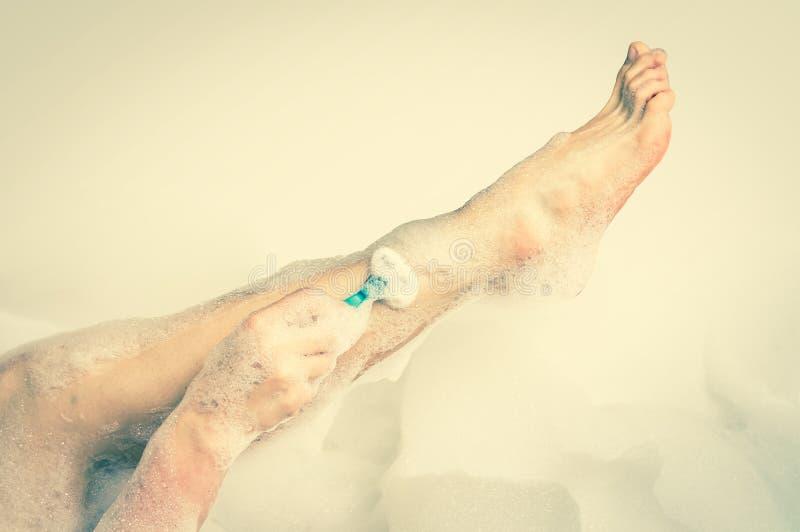 Mujer que afeita las piernas con la maquinilla de afeitar en cuarto de baño - estilo retro imagenes de archivo