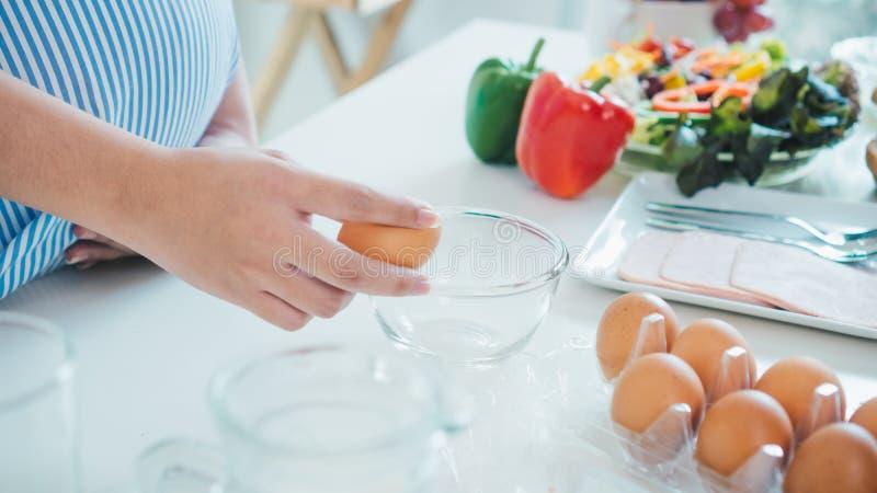 Mujer que agrieta un huevo en un cuenco con hacer una pausa en cocina foto de archivo