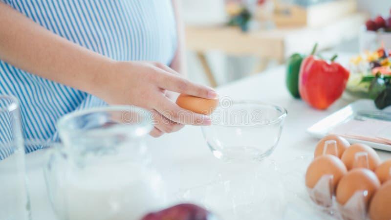 Mujer que agrieta un huevo en un cuenco con hacer una pausa en cocina imagenes de archivo