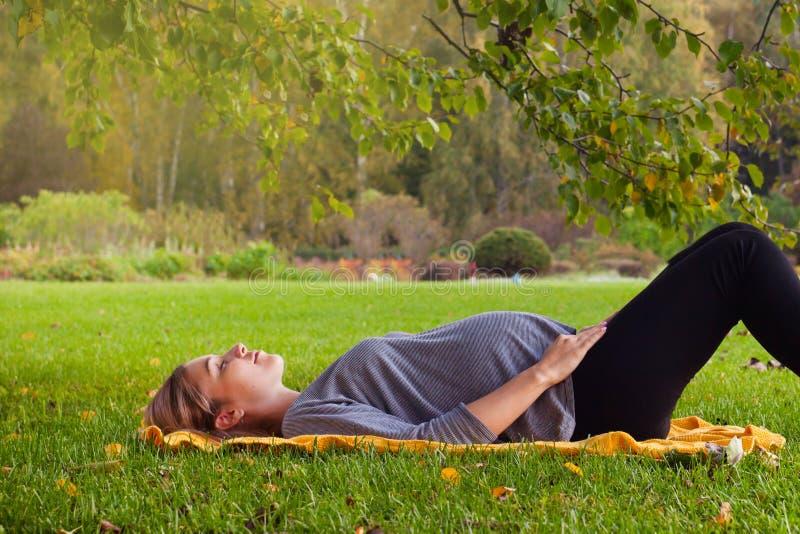 Mujer que aguarda para un bebé, hembra embarazada linda que se acuesta en hierba verde fresca en el pregna del jardín, del día so fotos de archivo libres de regalías
