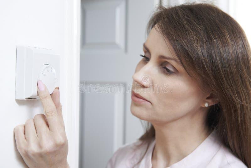 Mujer que ajusta el termóstato en control de la calefacción central fotografía de archivo