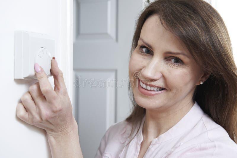 Mujer que ajusta el termóstato en control de la calefacción central fotografía de archivo libre de regalías