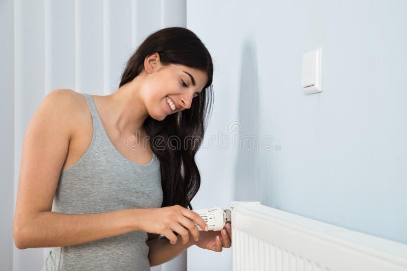Mujer que ajusta el termóstato en el radiador imágenes de archivo libres de regalías