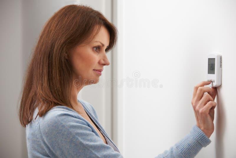 Mujer que ajusta el termóstato en la calefacción central imagenes de archivo