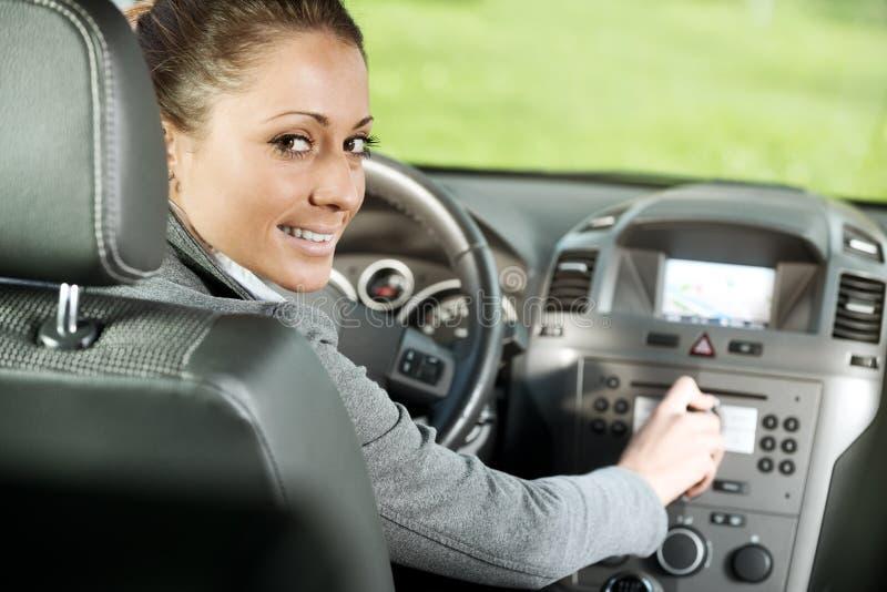 Mujer que ajusta el volumen de radio en el coche fotos de archivo