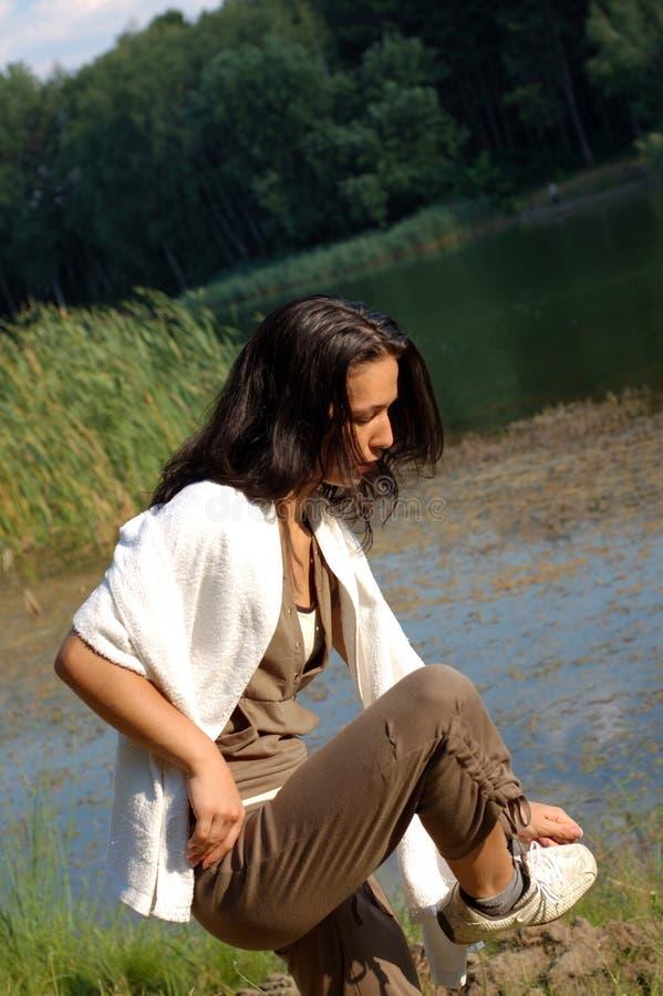 Mujer que ajusta el zapato por el lago foto de archivo