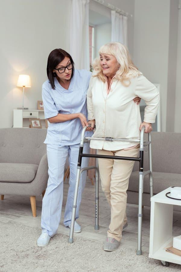 Mujer que anima de la enfermera cuidadosa más vieja fotos de archivo