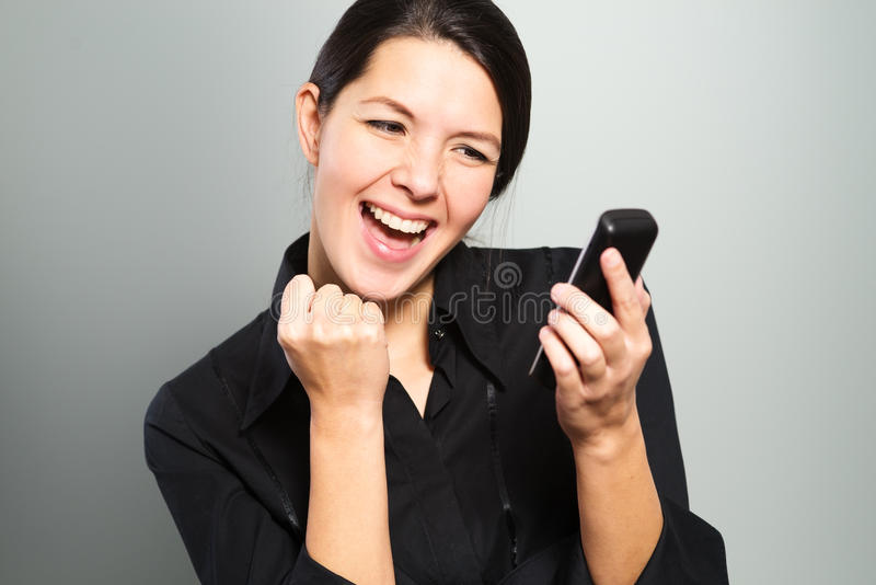 Mujer que anima en las buenas noticias en su móvil imágenes de archivo libres de regalías