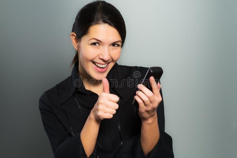 Mujer que anima en las buenas noticias en su móvil imagen de archivo libre de regalías